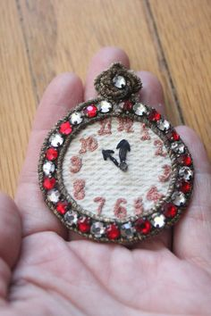 This 50s red and clear rhinestone embroidered pocket watch applique is just adorable! The numbers are all embroidered and the hands are as well. The