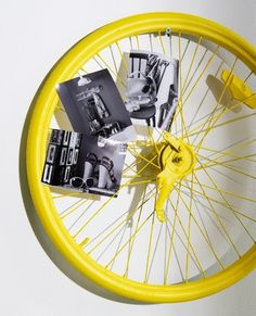 Upcycled wall art. Paint an old bicycle wheel, and double it as a photo holder.