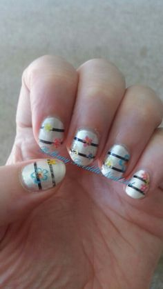 White + black stripe design with flowers, blue, pink and yellow. Cute spring / summer nail art.