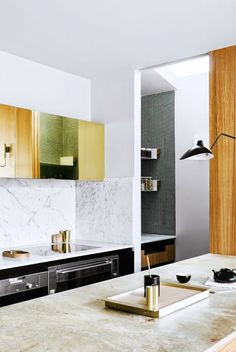 Elegant marble counter tops, metallic gold cabinets and wood wall