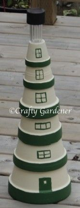 lighthouse made from varying sizes of clay pots with a solar light on the top, http://www.craftygardener.ca
