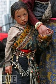 Tibet child wearing a traditional side robe. I like the leopard print lining the robe with leather and bead decoration.