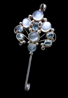 Dorrie Nossiter. Arts and Crafts kilt pin brooch.  Silver, moonstone and aquamarine, c. 1930. Fitted case.