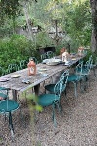 Teal velvet outdoor furniture. Crustic table. Gravel patio.