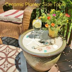 Turn a flower pot into a table by filling it with sand, adding seashells and placing a glass top on it.