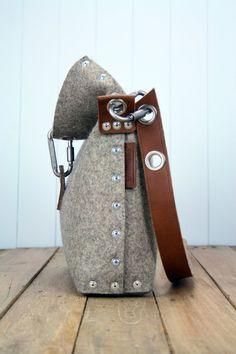 Voelde handtas die is handgemaakt in Londen, van industriële wol vilt van 3 mm en wordt gemonteerd met behulp van pop klinknagels. De riem is gemaakt en gekoppeld aan de zak toevoegen met behulp van 100% plantaardig gelooid volnerf leder die wordt ondersteund met vilt een ander tactiele gevoel.  De zak plooien vastmaakt met carabiner en er zijn twee binnenzakken voor uw telefoon en portemonnee, evenals pen houders en een ruimte om te houden van uw reiskaart.  Afmetingen:  Lengte 10/ 25cm…