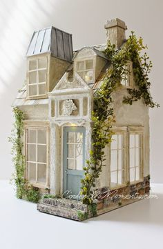 Who says all dollhouses have to be pink?! Maybe you live in boxy modern efficiency but are dreaming about white lace and roses on a mossy shoal somewhere. With this charming cottage from Cinderella Moments by Caroline Dupuis, you can welcome this breath of fresh air on a window ledge or side table and dwell in possibilities.
