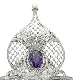 Detail view of AN AMETHYST AND DIAMOND TIARA Composed of four lattice design openwork palmettes with diamond detail and cultured pearl surmount, each centering upon an oval-shaped amethyst, to the pavé-set diamond scrolling base and line bandeau, inner circumference 44.5 cm