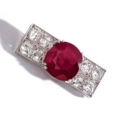 Platinum, Ruby and Diamond Brooch, Chaumet, France, Circa 1920. Set in the center with a 10 carat cushion-shaped Mogok ruby, flanked by 4.40 carats of old mine diamonds. With fitted box signed J. Chaumet, the front stamped 'Anne'.