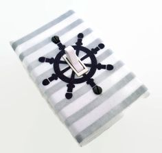 Here is a nautical switch plate / light switch cover made with a nautical theme featuring a dark grey ships wheel or helm on a grey and white
