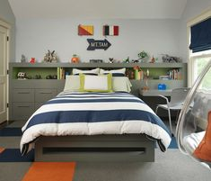 Gorgeous boy's bedroom with wall length gray built-in headboard featuring drawers to the left and a floating desk to the right with open upper shelf accented with a green interior. A wooden arrow and wooden flag signals hang over the gray platform bed which is dressed in navy rugby stripe bedding topped with a green bordered pillow over hardwood floors layered with gray, orange and navy carpet tile with an acrylic hanging bubble chair in the corner opposite the bed.