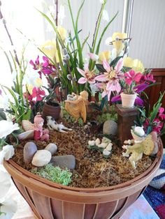 springtime indoor fairy garden. The fairy in the back is gathering pussy willows. The fairy on the left is laughing at the fairy on the right chasing the chicks.