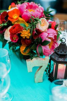 Bright + Colorful Golden Gate Garden Wedding: It was amazing to see the most breathtaking coral peonies featured prominently throughout the space when we arrived at the reception. The corals, reds, pinks and oranges of the floral table arrangements looked amazing against the turquoise of the table runners. Pics: Milou + Olin Photography