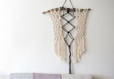 Emily Katz teaches how to make her signature bohemian wall hanging. This artwork is built upon a piece of found driftwood, and uses thick cotton rope and one simple knot to create an overall pattern. - Creativebug