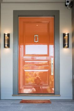 Modern sconces are mounted to white home siding on either side of a glossy orange lacquered door framed by a gray trim and accented with an orange floor mat.