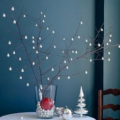 Give off the look of falling snow with our beautiful and elegant Christmas centerpiece. Fill a large, wide-mouth clear vase with white miniature ornaments. Stick bare winter branches into the vase, using the ornaments to keep the branches upright. Hang more ornaments from the branches; place a pomegrante in the vase for a pop of color.