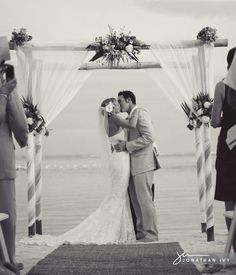 Love the arch...and the dress...and the fact that the groom is smiling while kissing the bride