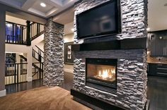 stacked stone accent wall with flat screen tv and fireplace. dark wood floors and white stairs with wrought iron railing