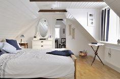 Dormitorio abuhardillado en azul y blanco.