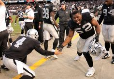 Oakland Raiders quarterback Derek Carr (4) and linebacker Khalil Mack celebrate on the sidelines after the team scored a clinching touchdown against the Buffalo Bills during the fourth quarter of an NFL football game, Sunday, Dec. 21, 2014, at O.Co Coliseum in Oakland, Calif. The Raiders won, 26-24. (D. Ross Cameron/Bay Area News Group)