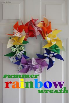 """Summer Rainbow Pinwheel Wreath. The instructions are for 5"""" paper squares, but can you imagine with fabric charms????"""