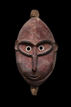 This engaging mask comes from the coastal area at the mouth of the Ramu River of Papua New Guinea's Madang Province. The mask has deep-set eyes, a thin loop nose, pronounced cheeks and a beautiful soft red surface. The piece dates to the early/mid 20th century.