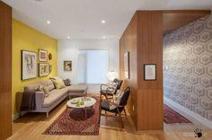 Fascinating yellow wall color decorates a small living room with fabric sofa and armchairs along with big wooden partition and recessed ceiling lamps ideas Breathtaking Yellow Walls Paint In Living Room yellow color schemes. living room ideas. yellow living room wallpaper.