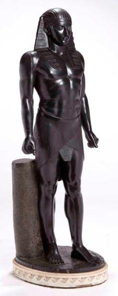 Figure d'un personnage pharaonique en basalte de patine noir, les bras pendant, les poignets serrés. Base ronde sur un socle de marbre blanc décoré d'une frise de postes. Socle en bois peint XVIIIe siècle. H: 122 - L: 36 cm