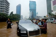 JAKARTA, INDONESIA - JANUARY 17: A Rolls Royce is stranded in floodwater in Jakarta's central business district on January 17, 2013 in Jakarta, Indonesia. Thousands of Indonesians were displaced and the capital was covered in many key areas in over a meter of water after days of heavy rain. (Courtesy: Ed Wray/Getty Images via Yahoo)