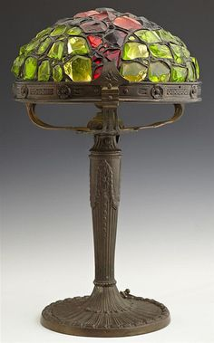 Patinated Spelter Chunk Glass Lamp, c. 1910, probably Austrian, the leaded shade within a relief decorated rim, on a tapered relief decorated support, to a like circular base.