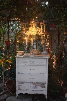 Make a lovely vignette in the garden  with white furniture, twinkle lights and candles