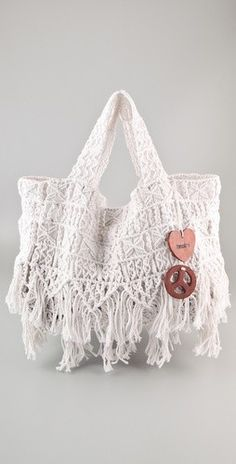"""Love by Diego Binetti- Amacca Bag. This Macramé Bag Features Fringe Trim at the Bottom. Wooden Heart and Peace Sign Charms at Double Handles. Interior Features Key Ring and Leather Bottom Panel. 9""""H x 21"""" x 7""""D. 7"""" Drop from Handle. Weight: 42 oz / 1.2 kg"""