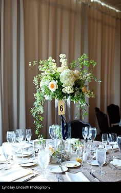 Tall floral centerpieces in buttercream, soft apricot, green and white by Visual Impact Design, Sacramento Wedding Florist