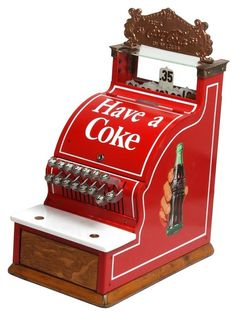 Coca-Cola Advertising National Cash Register Model 717. Beautiful countertop model is completely restored with bold red paint, white stenciling reads Have A Coke and has bottle-in-hand decals on the sides. Gilt brass crest piece over the glass numbered flag display reads Drink Coca-Cola in Bottles, 5c. Serial number 2049017. measures 20.5 in. high x 10.5 in. wide x 16 in. deep.