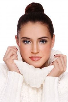 Lovely young woman with magnetic blue eyes, wearing a warm white pullover