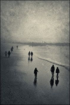Surreal scene of an early morning stroll on a dark foggy beach.  It is overlaid with rich texture and a blue and sepia tone.