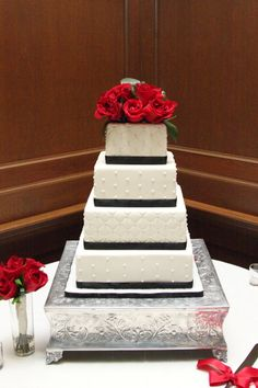 Quilted and pearl accent fondant with black ribbon and red roses on a square four-tier cake | villasiena.cc