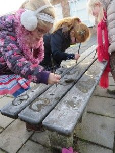 Offside - Toddlers paint letters on frozen benches with warm water and a brush, kleuteridee.