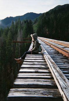 Chica sentada en las vías del tren en medio del bosque