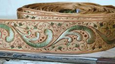 Vintage French jacquard trapunto ribbon trim with beige base and green - bronze ombre rococco swirl motif highlighted with subtle chocolate