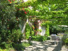 Le rose rampicanti sulla facciata di mescolano al verde della pergola