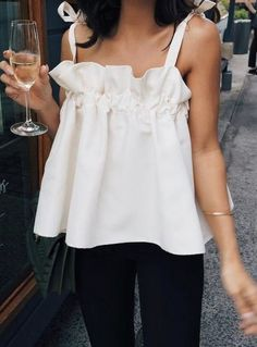 Feminine details, such as ruffles, bows, voluminous sleeves, and all things frilly have been extraordinarily popular this season. This sleeveless blouse is one example of how statement blouses with an extra dose of femininity transforms an otherwise 'vanilla' ensemble into something special!