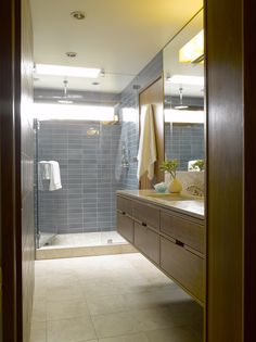 Mid Century Bathroom Remodel - Heath Ceramic Tiles, walnut-veneered Europly cabinets, slab travertine counter tops and backsplash, and travertine floor tiles, all inspired by the original designs of the house.