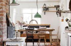 miętowe metalowe lampy wiszące, drewniany wiejski stół z krzesłami,ściana z czerwonej cegły i dodatki w stylu vintage