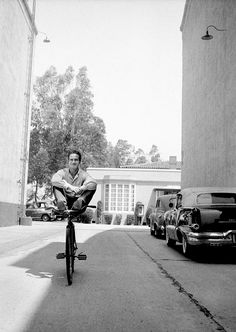 Paul Newman is photographed by John Hamilton riding a bike with no hands on the Warner Bros lot, 1958.