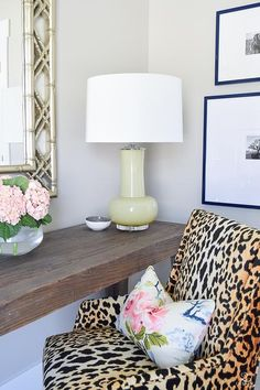 Chic work space boasts a leopard print chair in Tonic Home Bianca Fabric lined with an Eastern Charms Hibiscus Pillow paired with a salvaged wood desk topped with a yellow green lamp tucked under a silver bamboo lattice mirror.