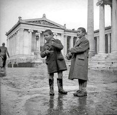 Παιδιά που κρατούν τρίγωνα και τραγουδούν κάλαντα στην Αθήνα του 1950.Φωτογραφία: Κωνσταντίνος Μεγαλοκονόμου. Αρχείο Μουσείου Μπενάκη.