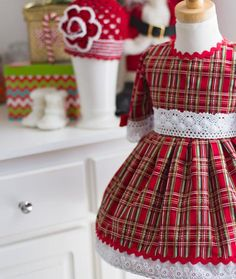 [short_description]Celebrate sweetly in this classic red plaid Christmasdress. [/short_description][product_description] Lots of details to this dress. Layers of crocheted lace and eyelet embroidered trim, as well as ric-rac. The cotton plaid fabric has highlights of gold and is just perfect for any holiday occasion.Matching Hair Accessory is available.   Details: fully lined back buttons 100% cotton fabric Please allow 3-4 weeks for delivery.[/product_description]