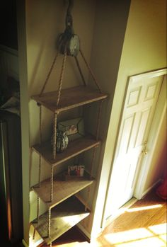 This is a hanging shelf supported by a beautiful antique pulley and manila natural untreated rope