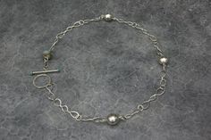 Figure Eight Chain with Spheres: Sterling silver chain features figure-eights links and hand-made sterling spheres . Clasp has a turquoise-studded stem hung from a turquois...